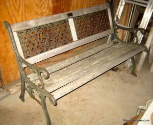 Leisure Ways park bench with iron sides, wood slats are weathered
