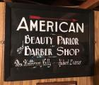 """American Beauty Parlor & Barber Shop"" sign on glass"